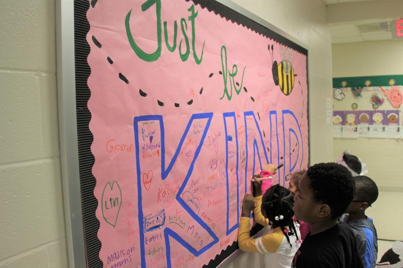 "Kindergartners at Batesburg-Leesville Primary School sign the ""Just Be Kind"" bulletin board that is on display in the school Media Center.  The bulletin board, which was created specifically for Random Acts of Kindness Week, serves as a reminder for students to cultivate kindness and to go out of their way to brighten other people's day."