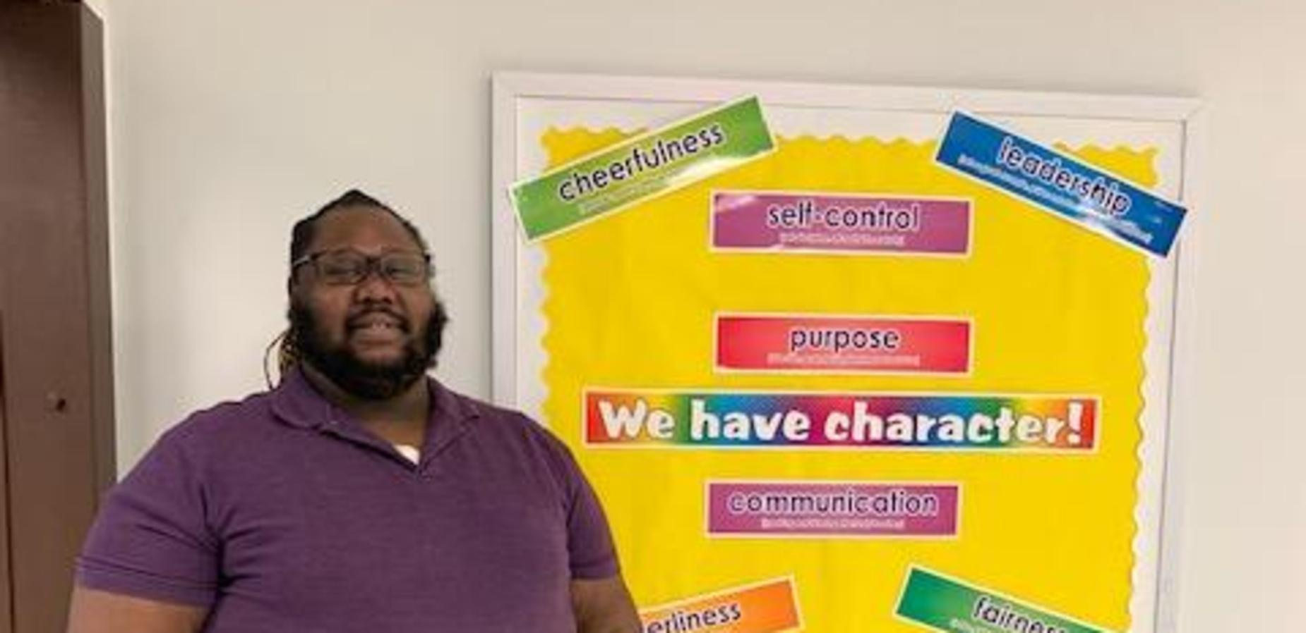Mr. Martin standing before the character board