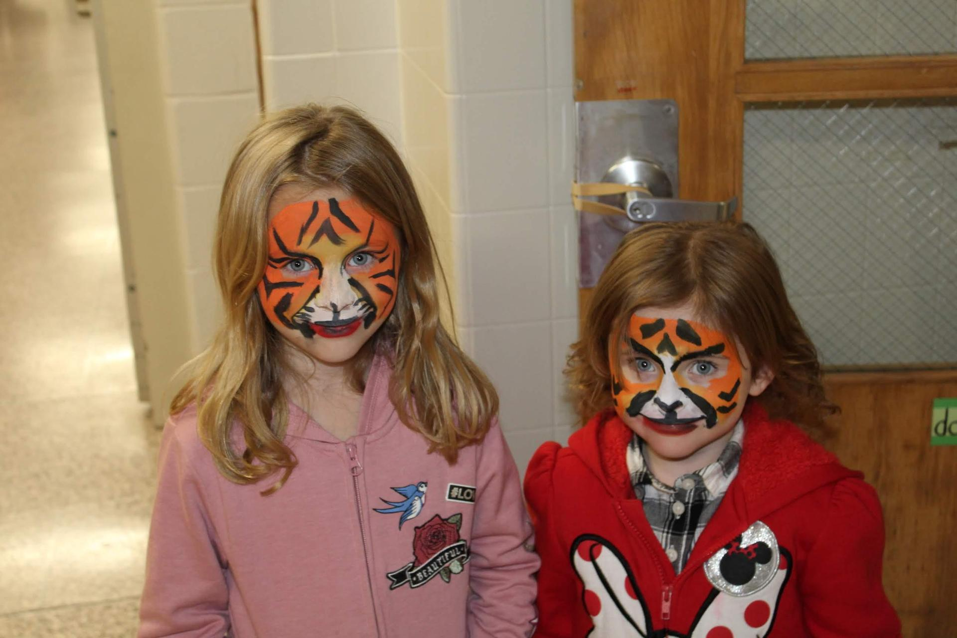 Sisters showing their face painting masterpieces.