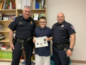 Two district police officers awarding a student a certificate of appreciation