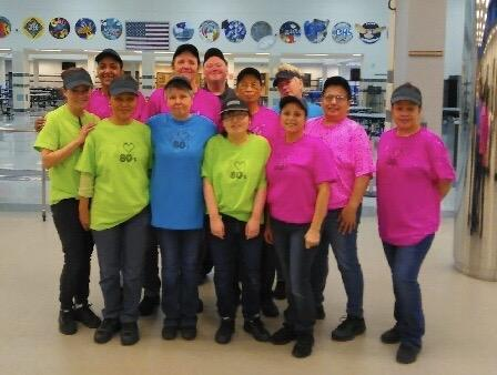 High school cafeteria staff in neon colored shirts for 80's Day