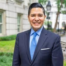 NYC School Chancellor Richard Carranza wearing a blue suit with a white dress shirt and blue tie.