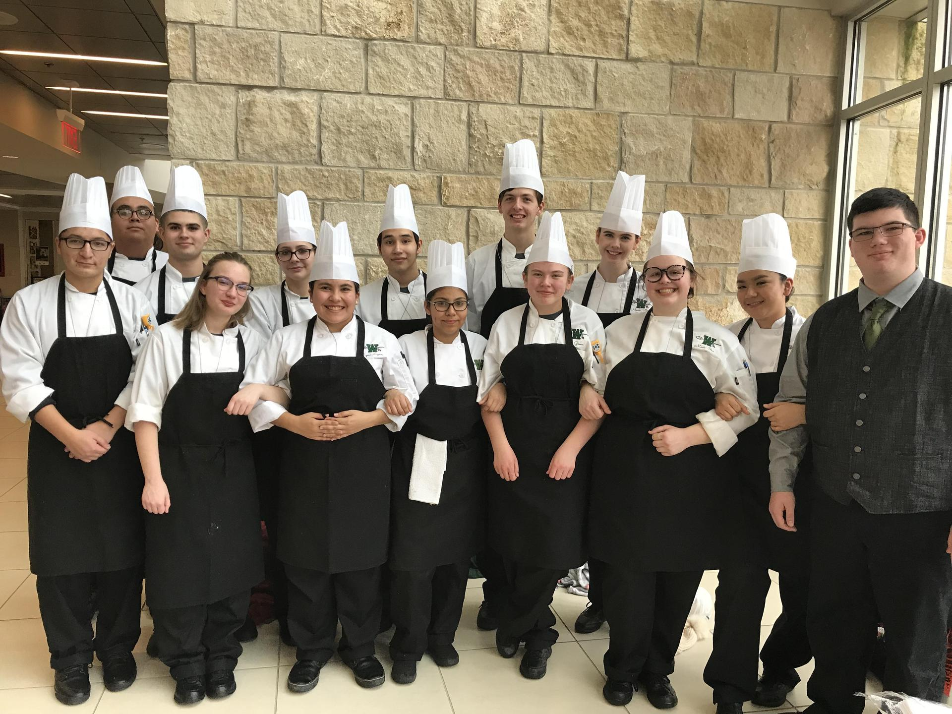 group of culinary students in aprons and chef hats