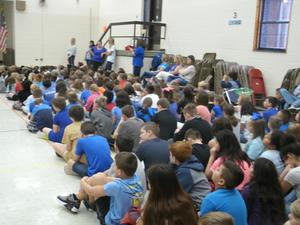 Students wear blue in multi-purpose room for anti-bullying presentation.