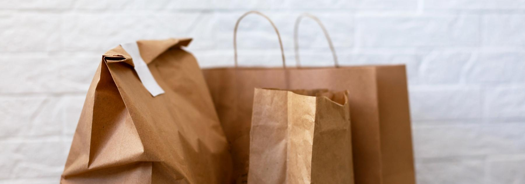 Brown paper bags on a table, signifying food to go