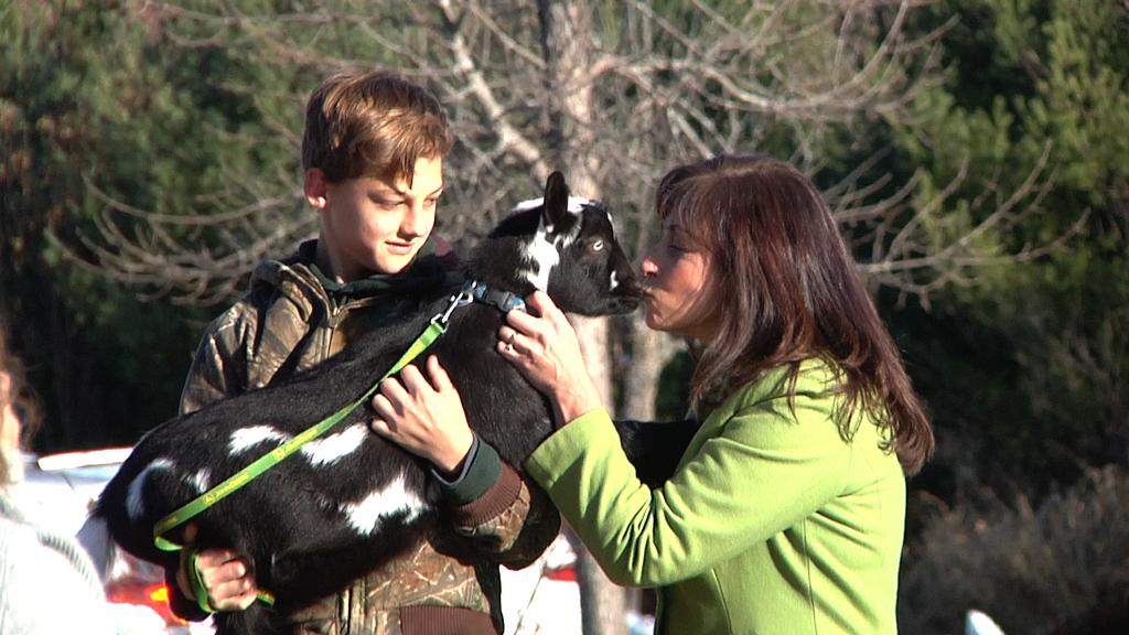 RES Assistant Principal Beth Peavey kisses a goat.