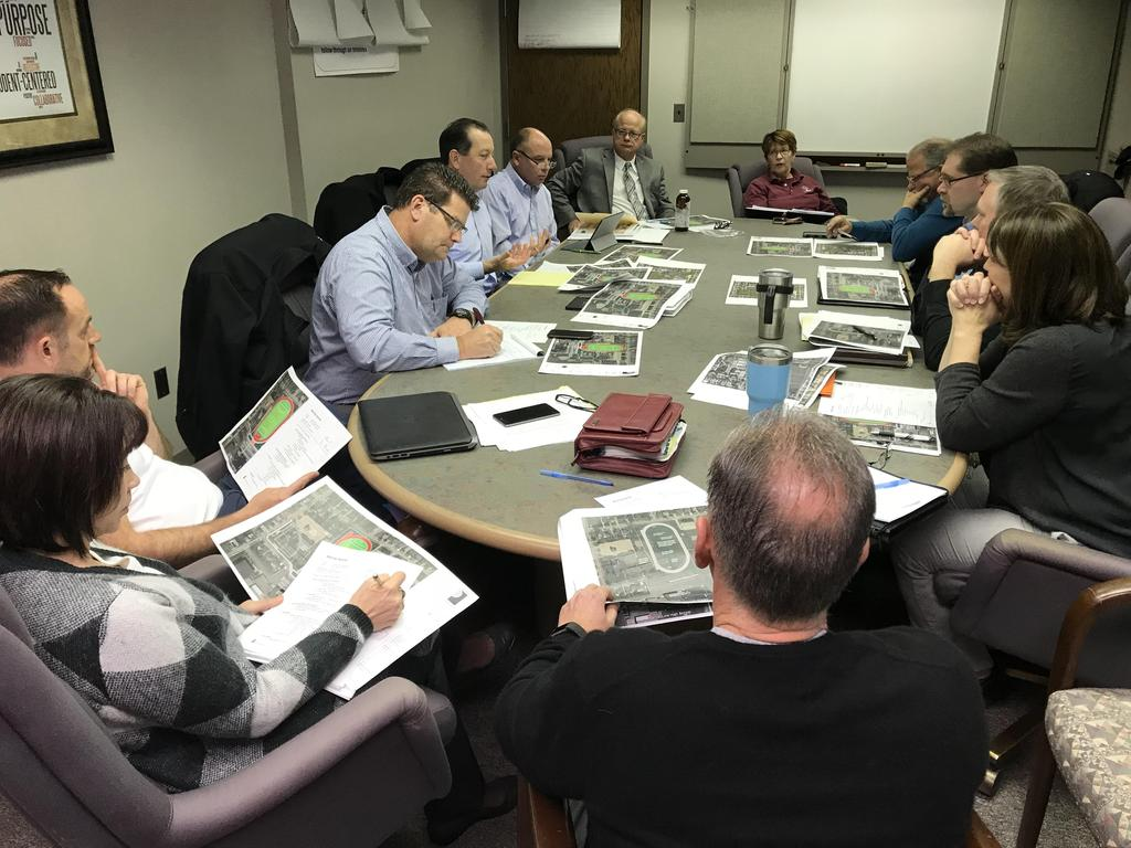 executives around conference table examining blueprints