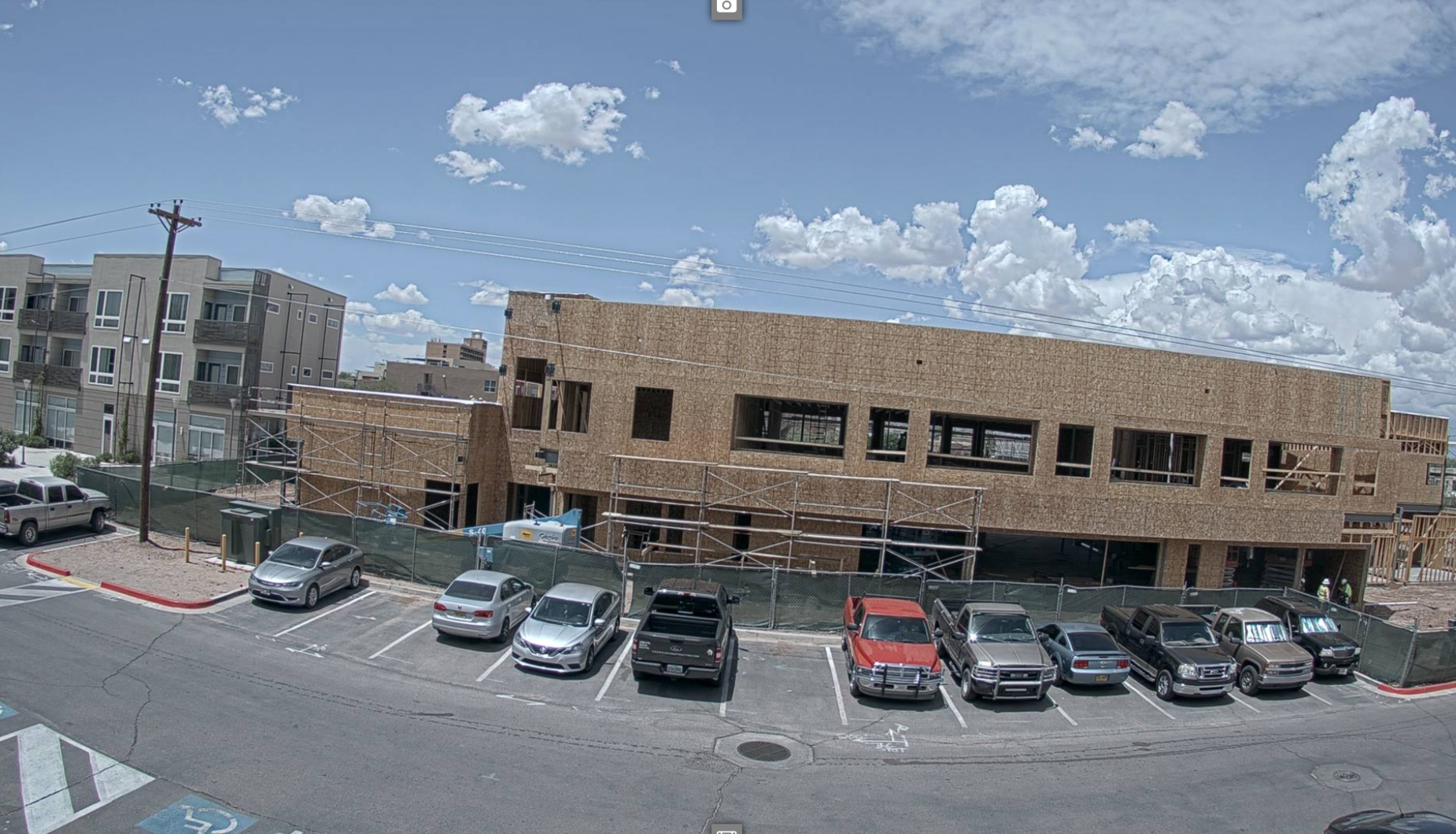 A photo of a building under a blue sky with some clouds. The building is under construction and the walls and framing are visible. Trucks and cars are parked in front of the building.