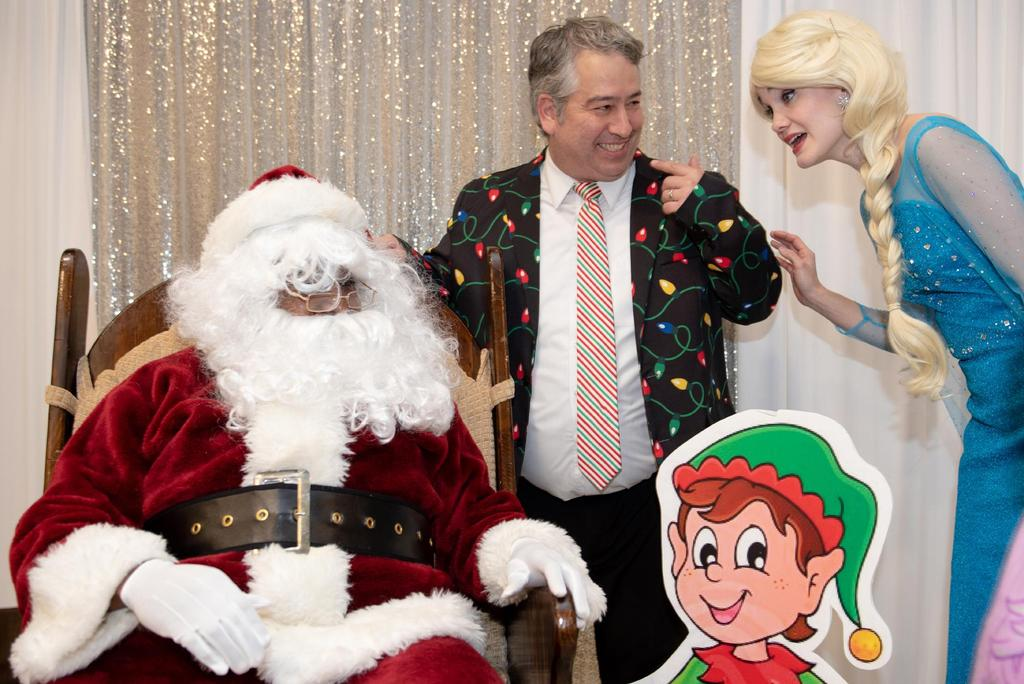 """Principal Alex Naumann interacts with Santa Claus and Elsa from """"Frozen"""""""