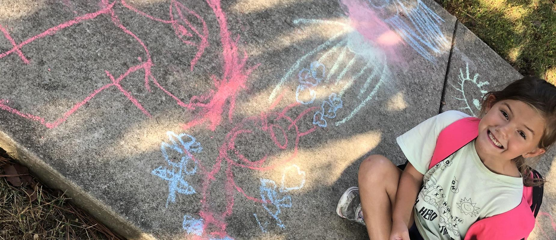 little girl and her chalk drawing