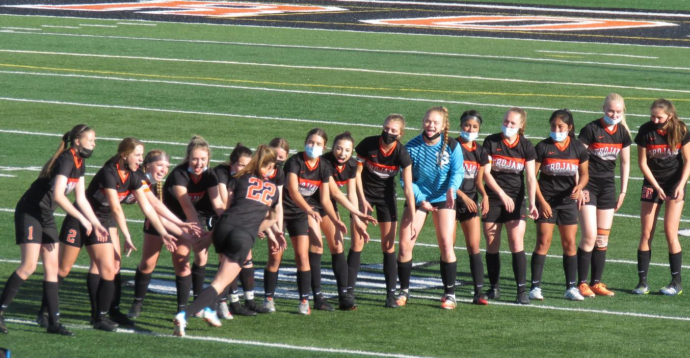 TKHS Soccer team players slap hands during introduction of starters.