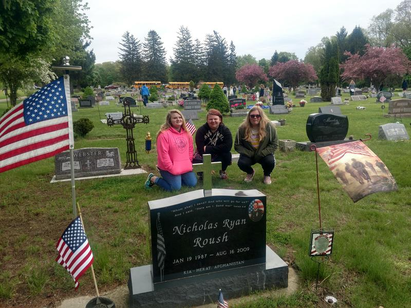 TKMS students top at the grave of Middleville-native Nicholas Roush as they place flags in the cemetery.