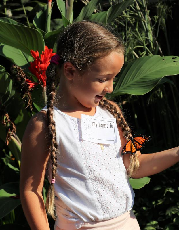 Tamaques 1st grader looks on in delight at a Monarch butterfly perched on her braid.
