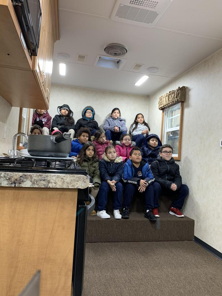 group of children quietly seated inside of the fire safety house