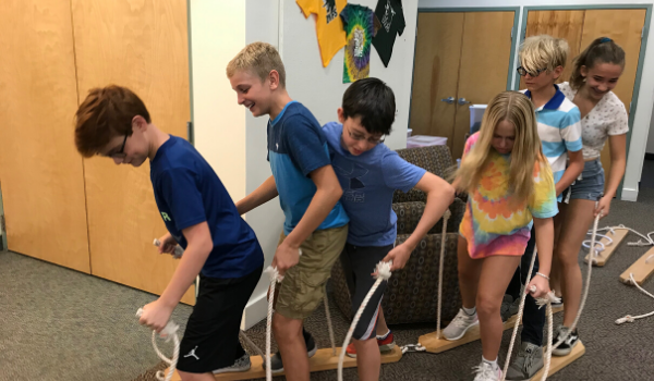 Students use teamwork to walk on skis in a team building activity.