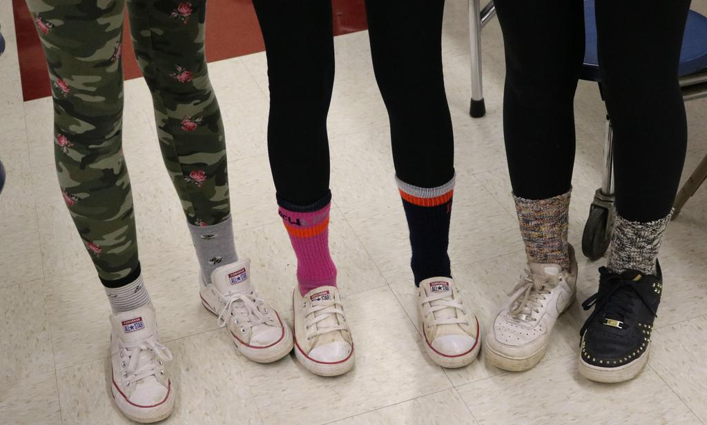 Photo of students' feet and ankles, showing mismatched socks and shoes on Mix It Up Day.