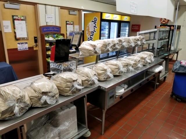 Pic of bagged meals sitting on a counter in school cafeteria.