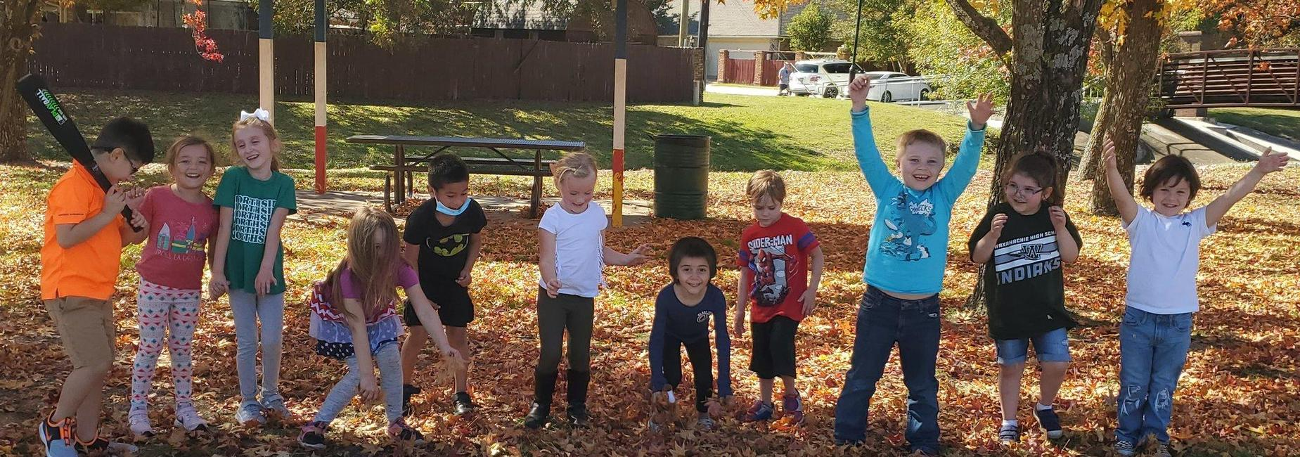 group of kiddos playing in fallen leaves