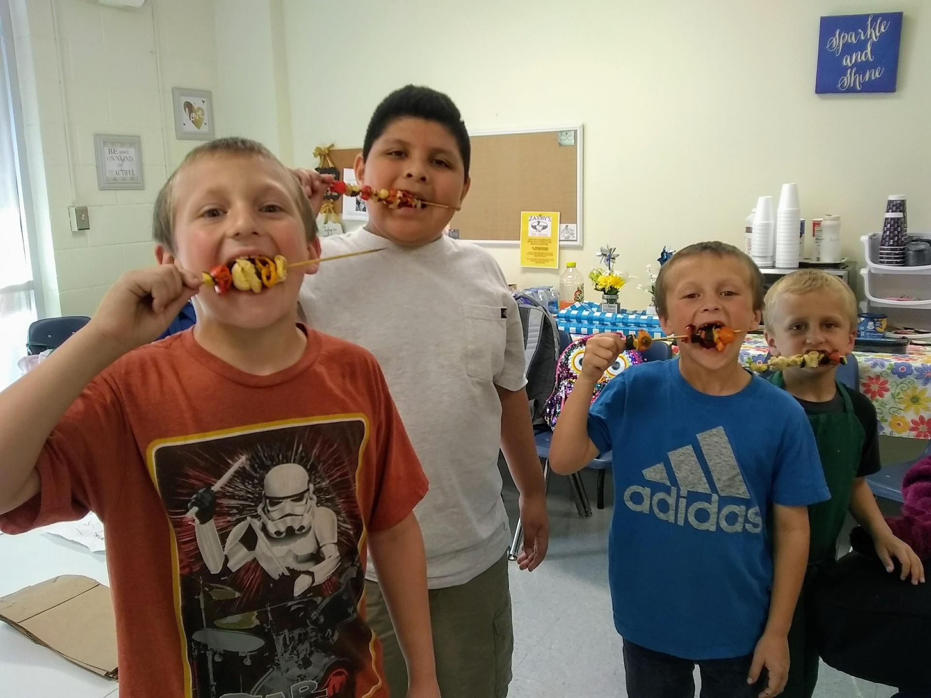 kids eating their cooked chicken kebabs