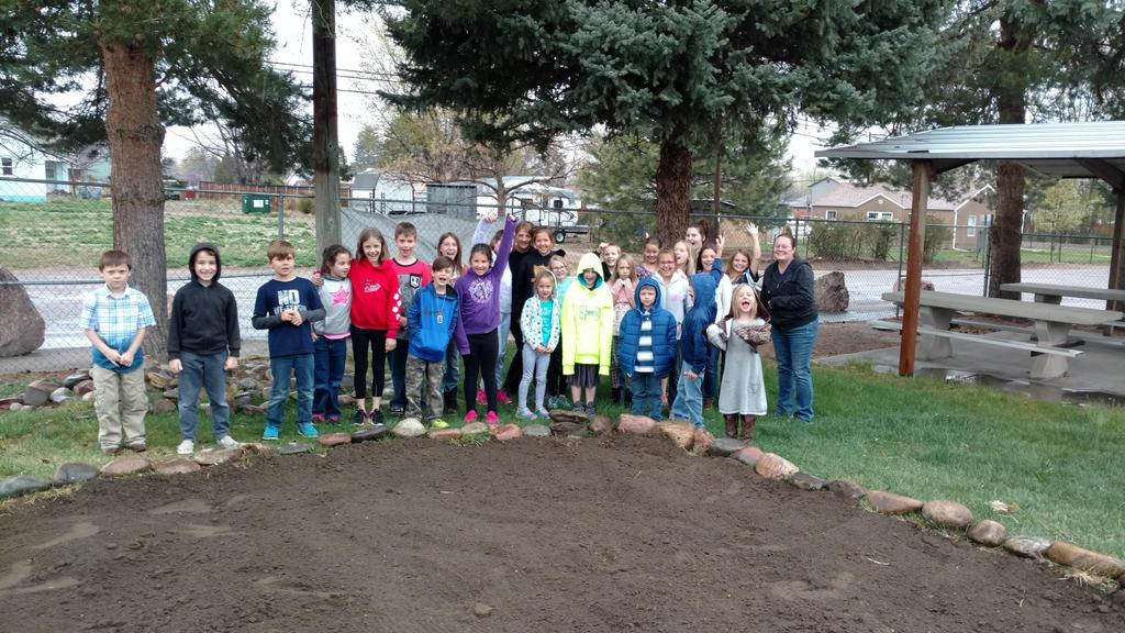 McKinley's graden club group picture next to new flower garden area