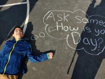 Student on concrete with chalk writing.