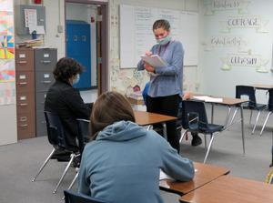 NHS math teacher Olivia Rogers hands out papers to two students.
