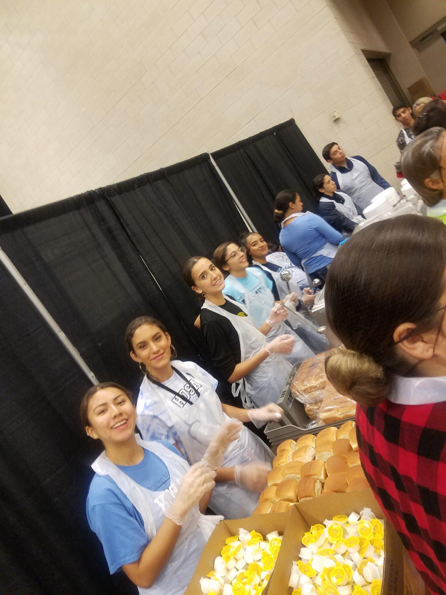 students in aprons volunteering