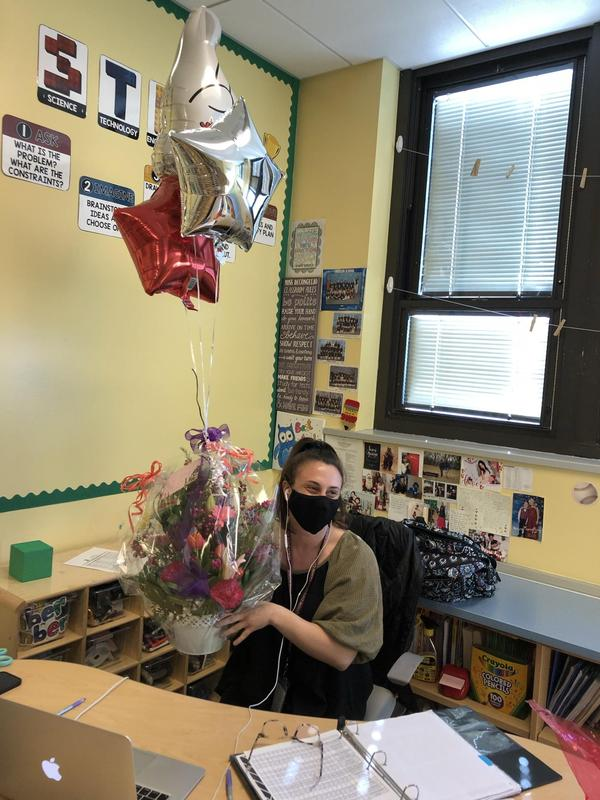 Ms. Decongelio holding flowers and balloons as she sits behind her desk