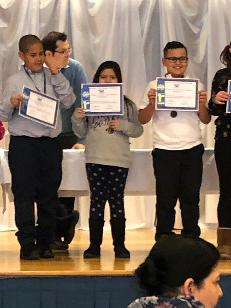 Edison student azcuena  first place certificate on stage with other winners