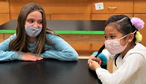 two fourth grade girls watch a dissection in science class
