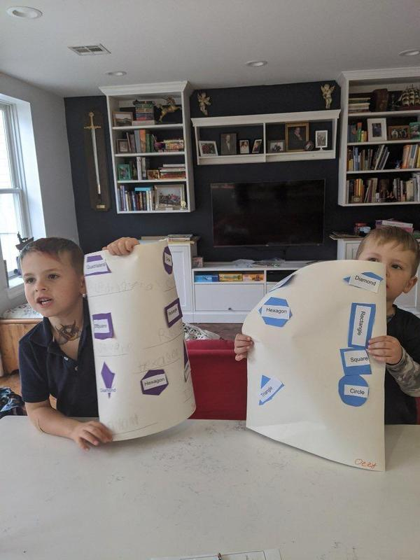 twin boys showing off their work