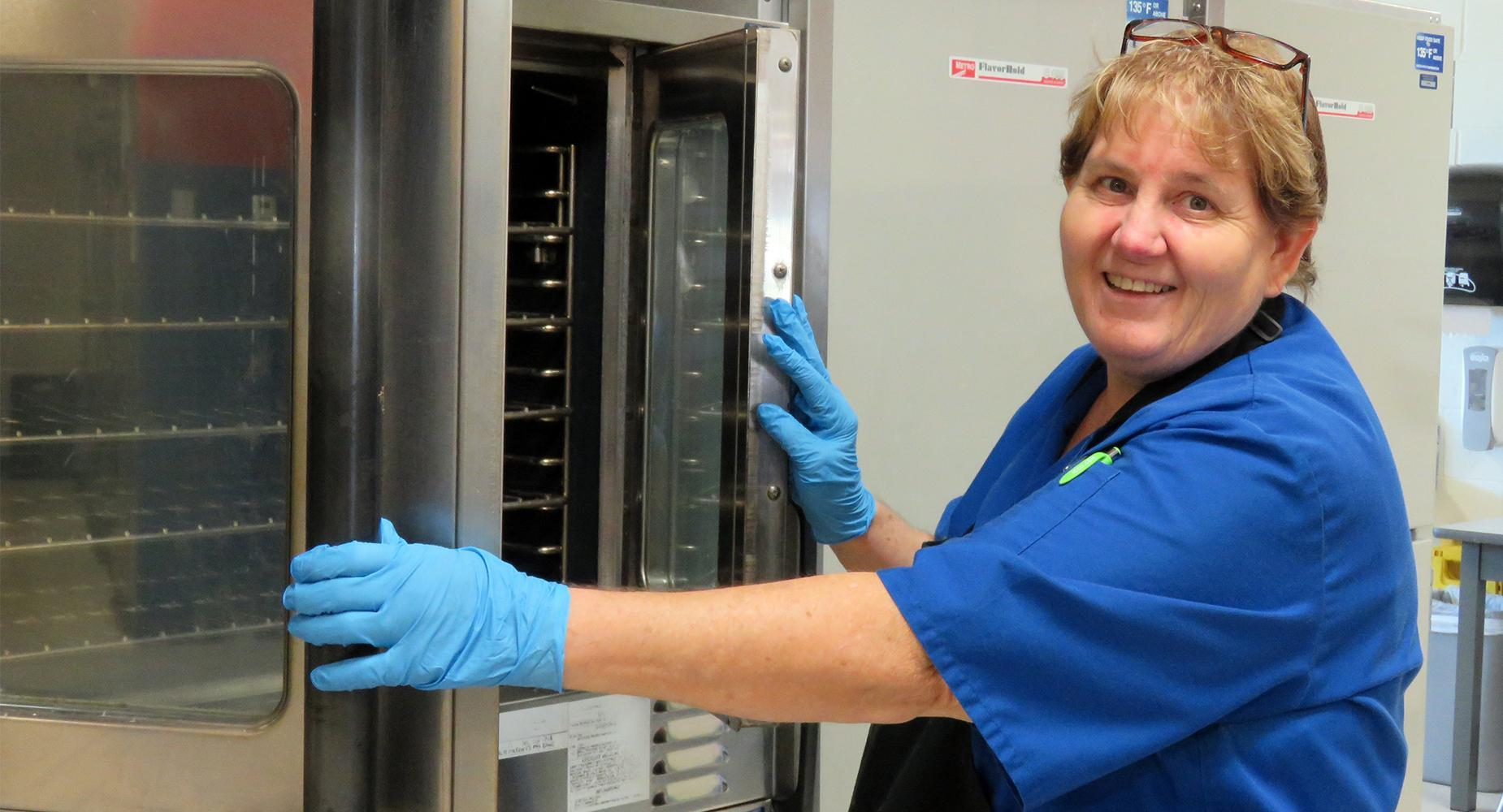 Woman in nutrition services blue smock pauses for the camera as she checks the oven.
