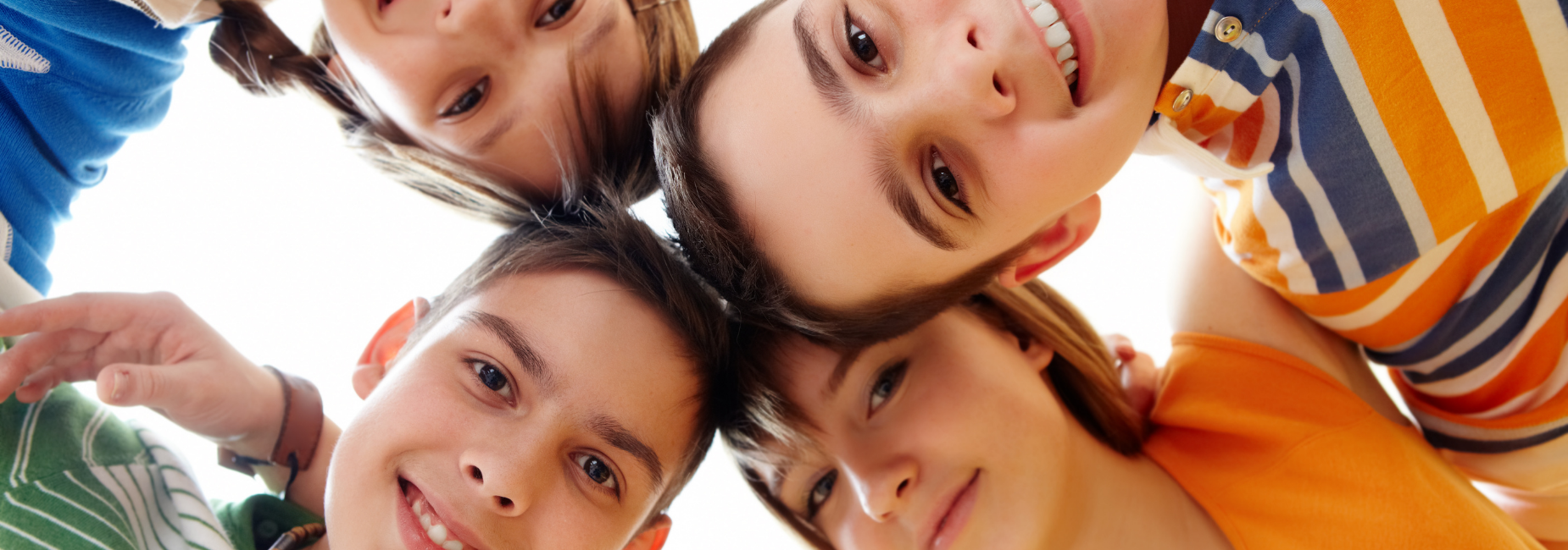 4 pre teens in a circle looking down at camera