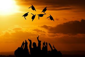 Silhouette of graduates tossing caps with a sunset in the background