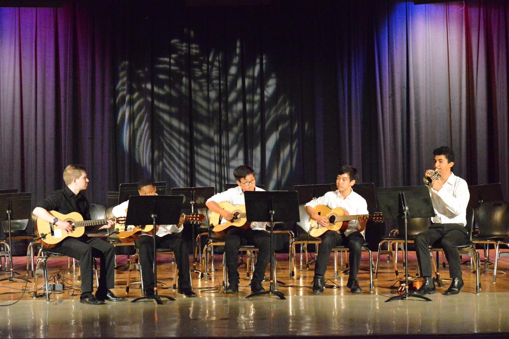Four students and music teacher, Mr. Lauchli, playing guitar and trumpet.