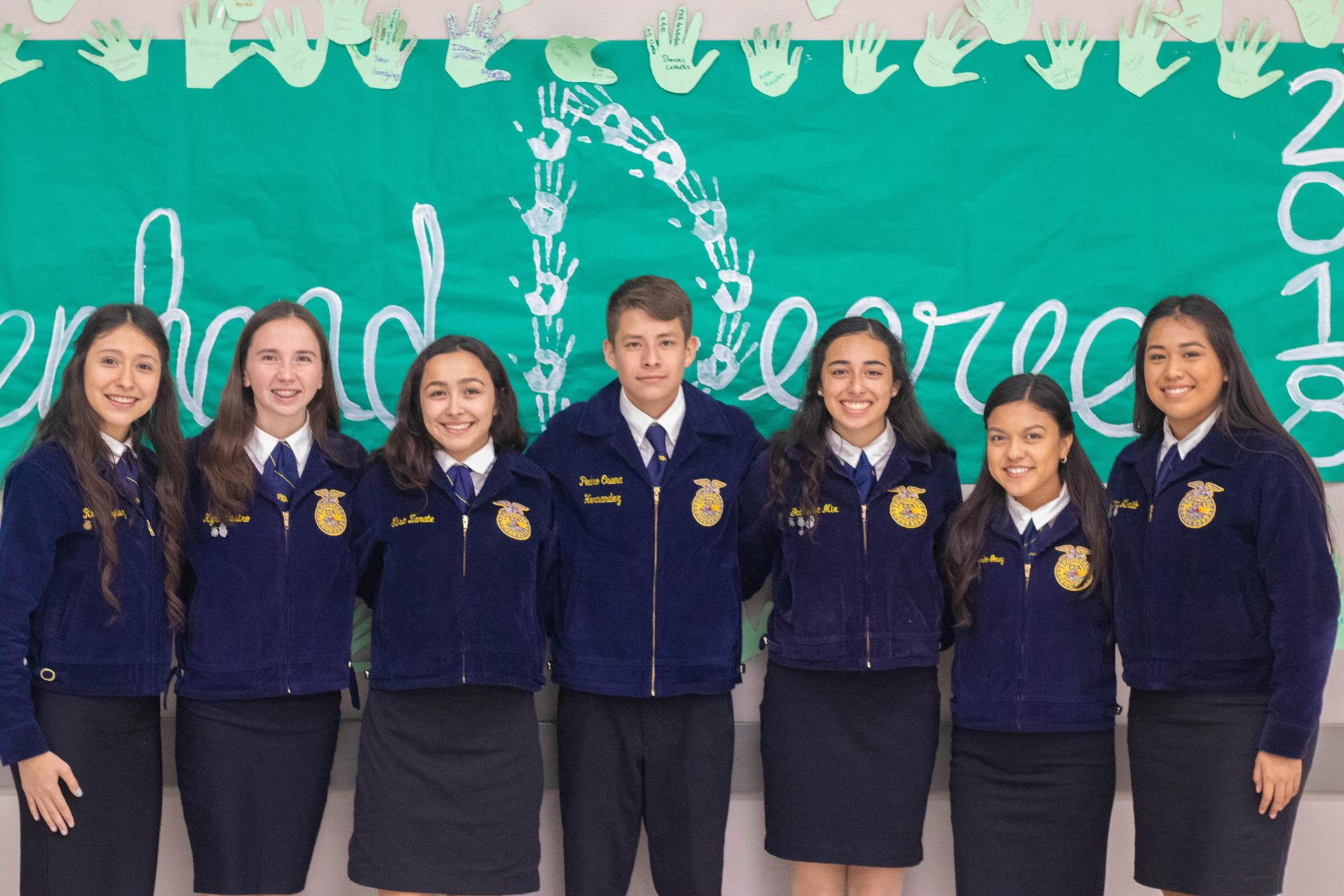 FFA leaders pose for picture behind Greenhand poster