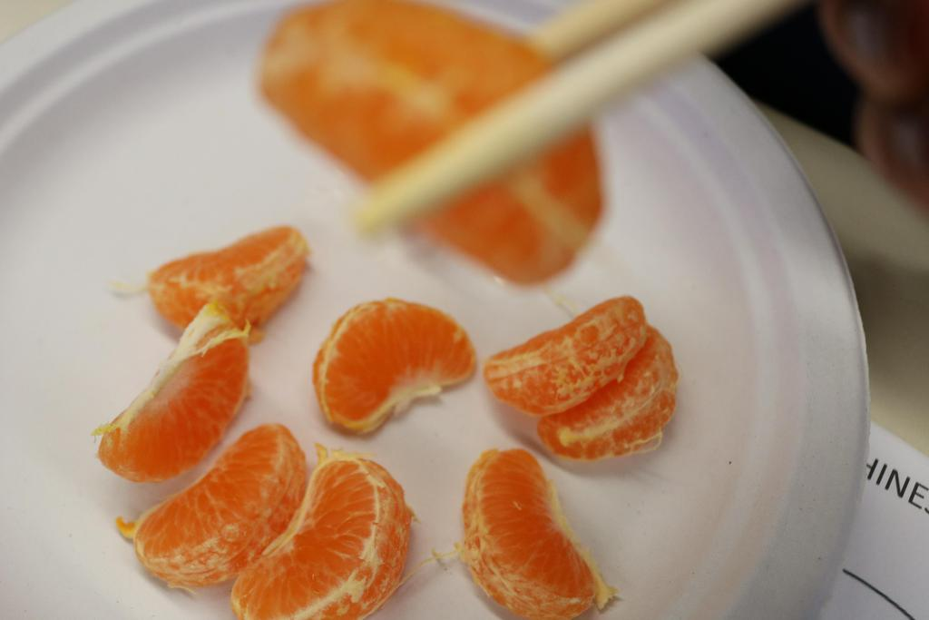 tangerine on plate and piece on chopstick