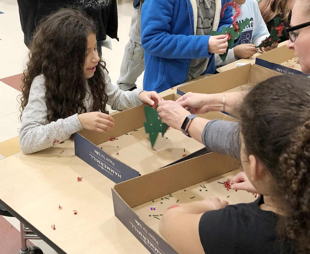 A teacher helps a student who's decorating a tree ornament at a crafts table