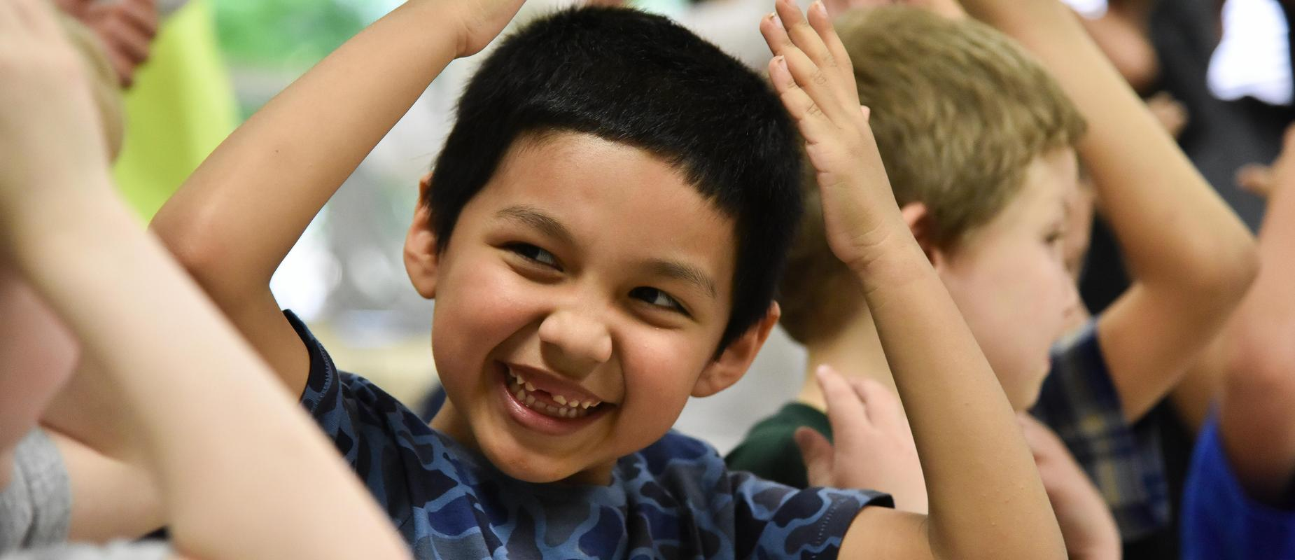 Young student smiling and putting his hands on his head