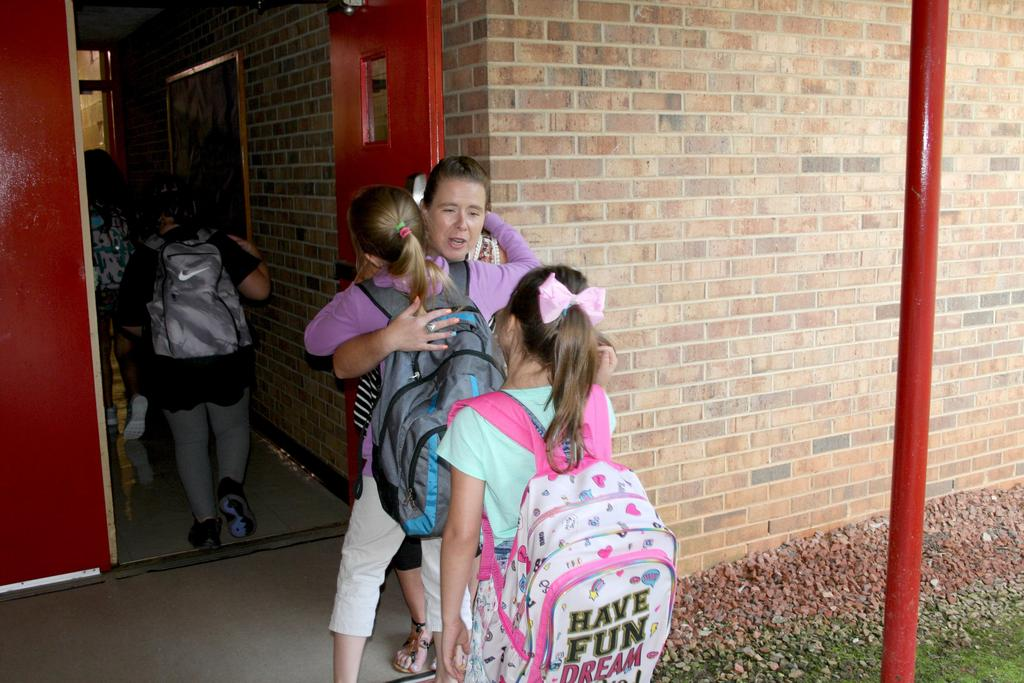 Teacher greets students with hugs upon arrival for the first day of school at C.B. Eller Elementary.