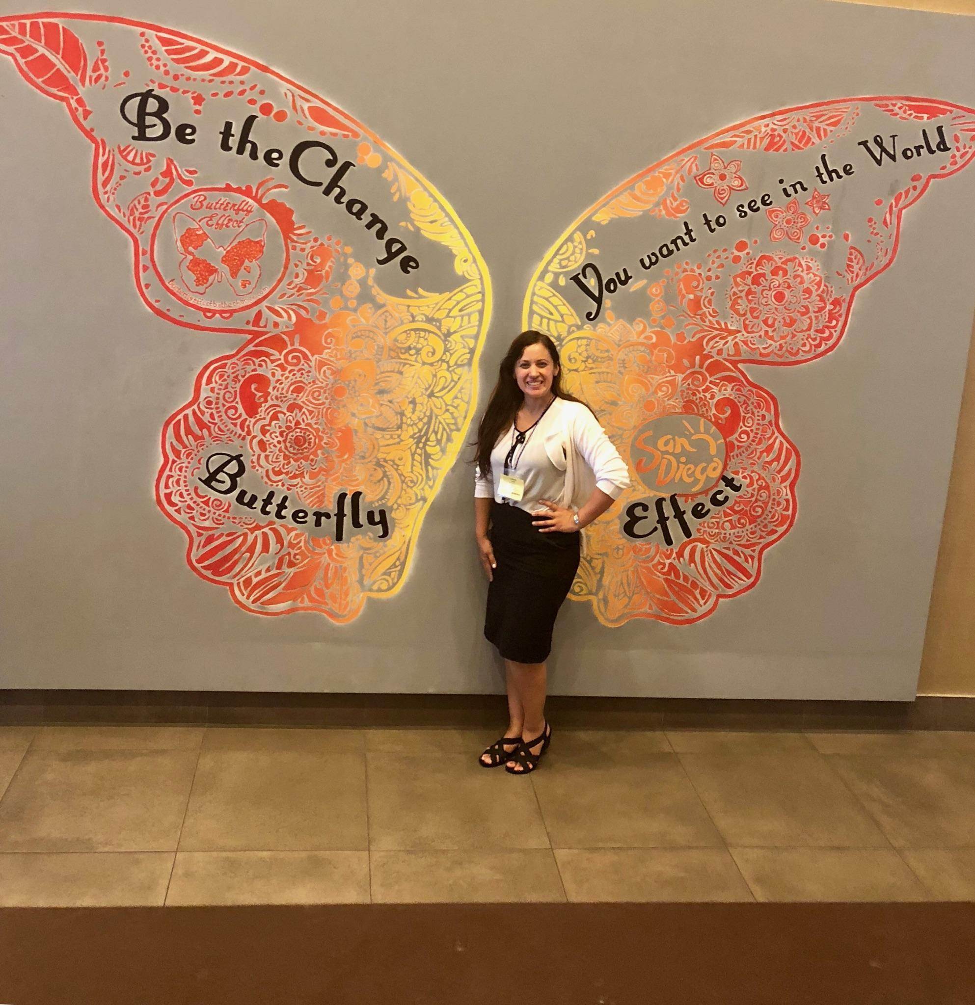 Laura Leon in front of a painted butterfly.