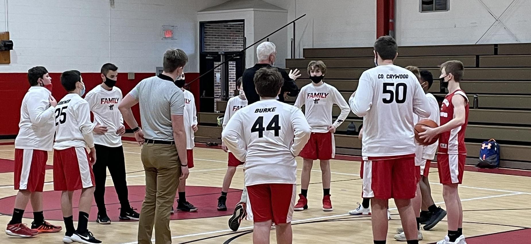A coach talks to a basketball team in a gym.