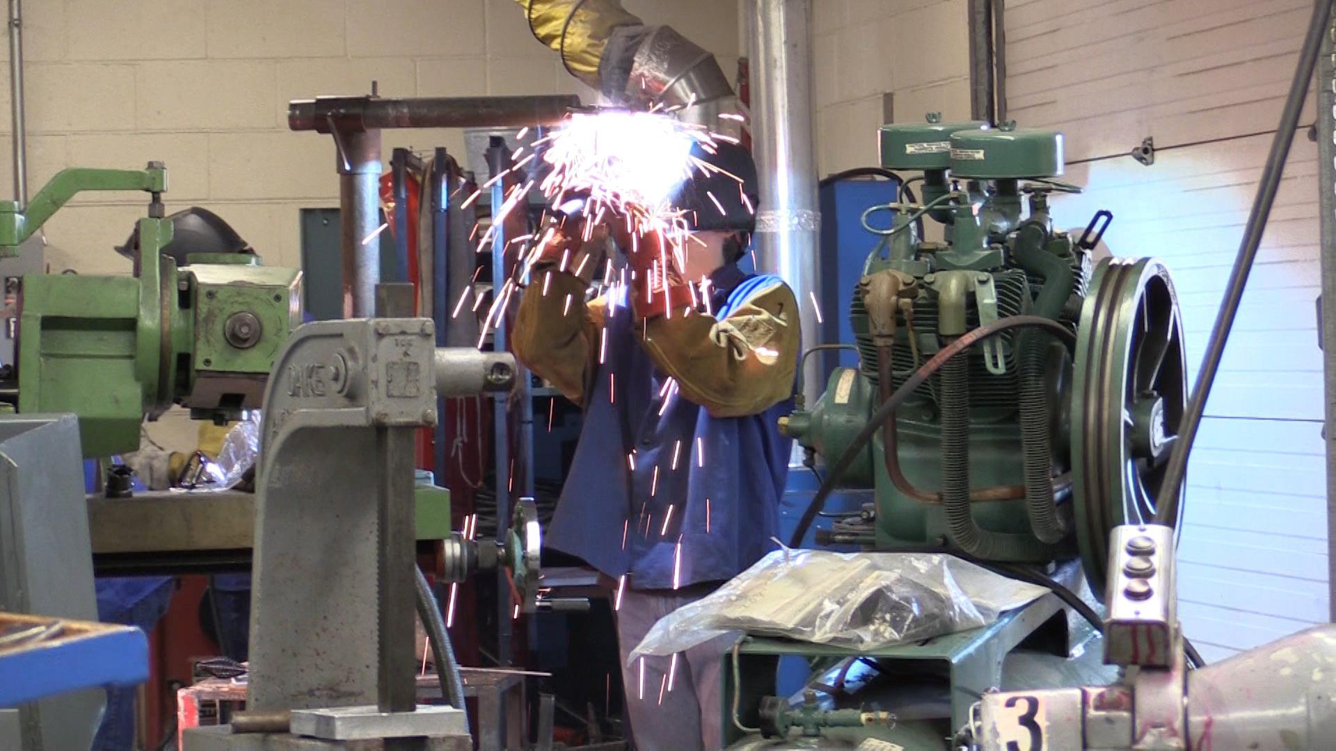 Student welding with sparks flying