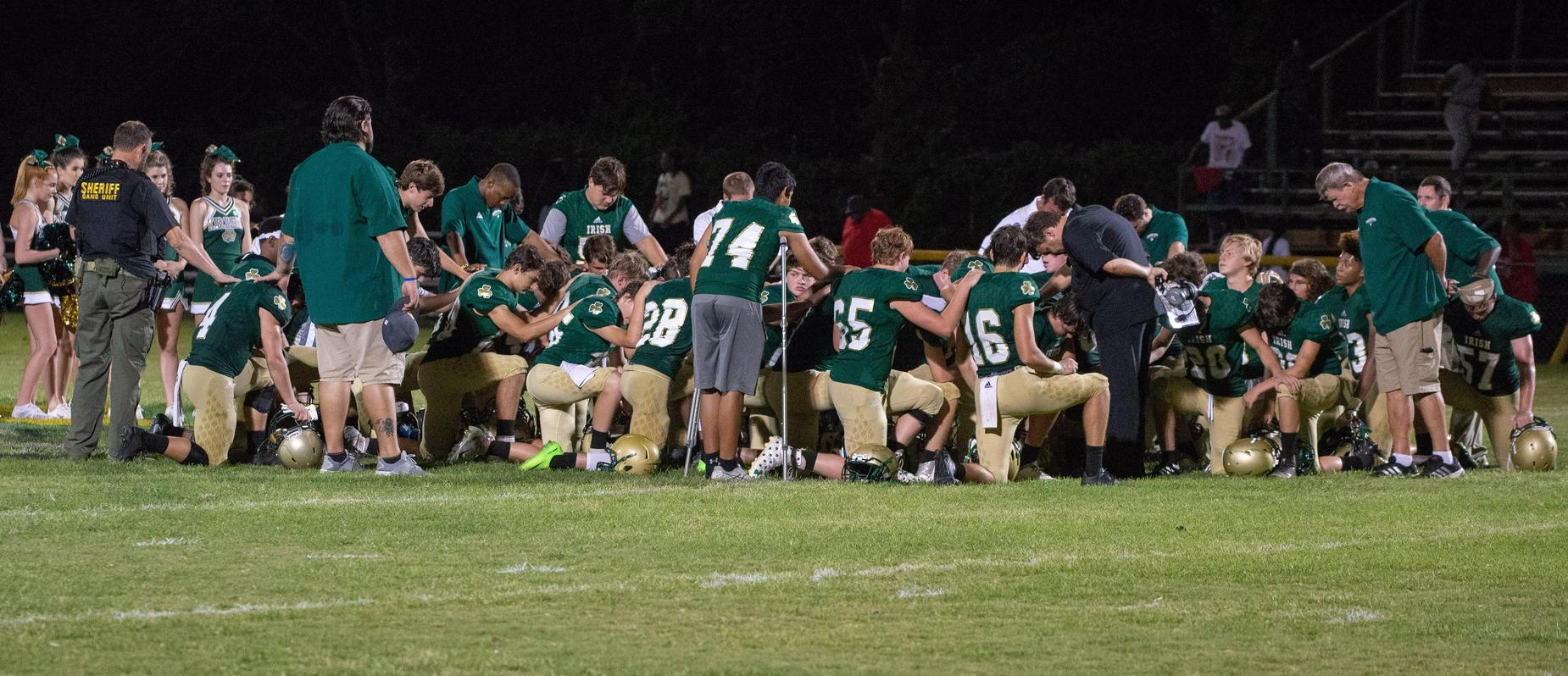 Football team praying after game