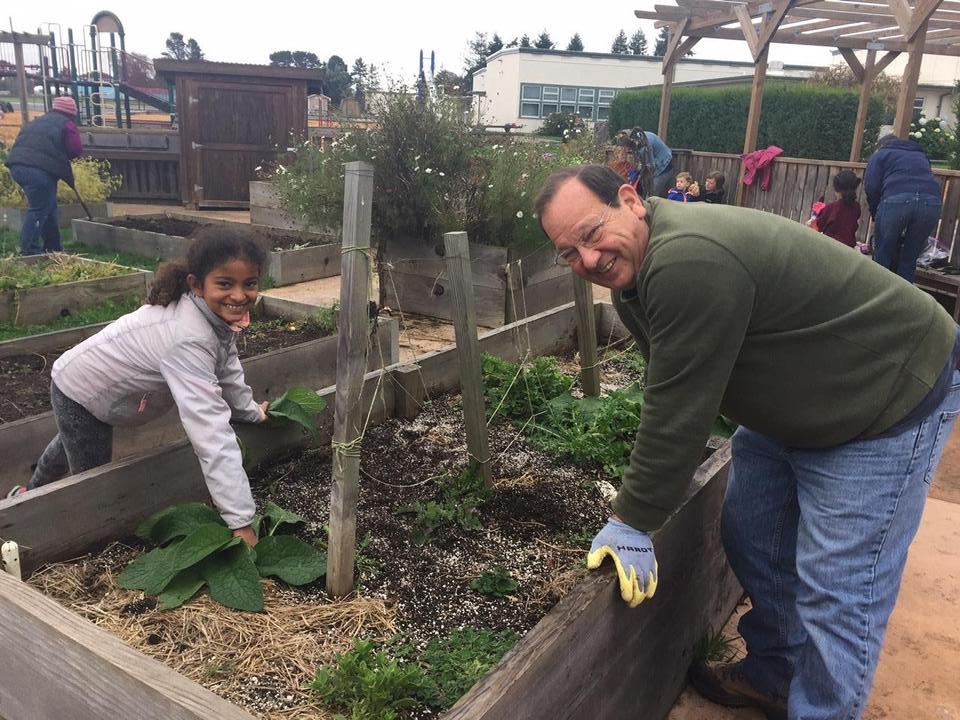 father and daughter weeding garden bed