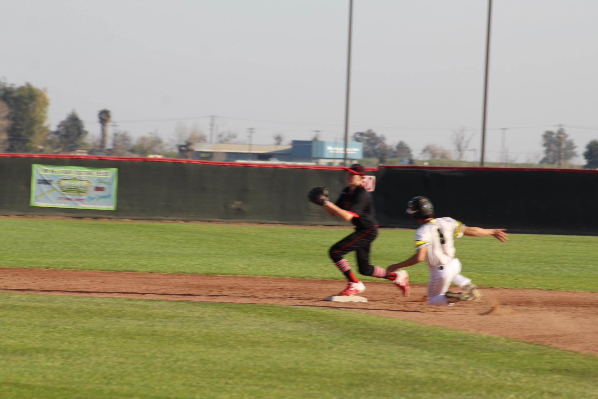 varsity baseball players in action against Sierra Pacificvarsity baseball players in action against Sierra Pacific