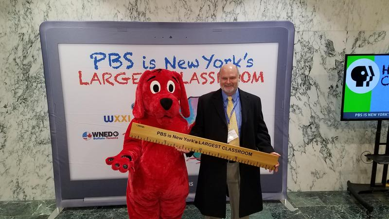 big red dog costume standing next to superintendent