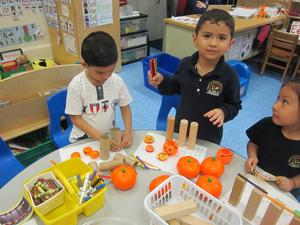 students begin building their structure to hold their pumpkins