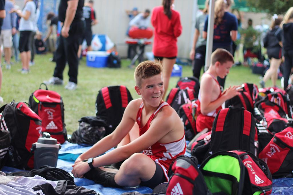 Smiling cross country athlete sitting on the ground surrounded by backpacks