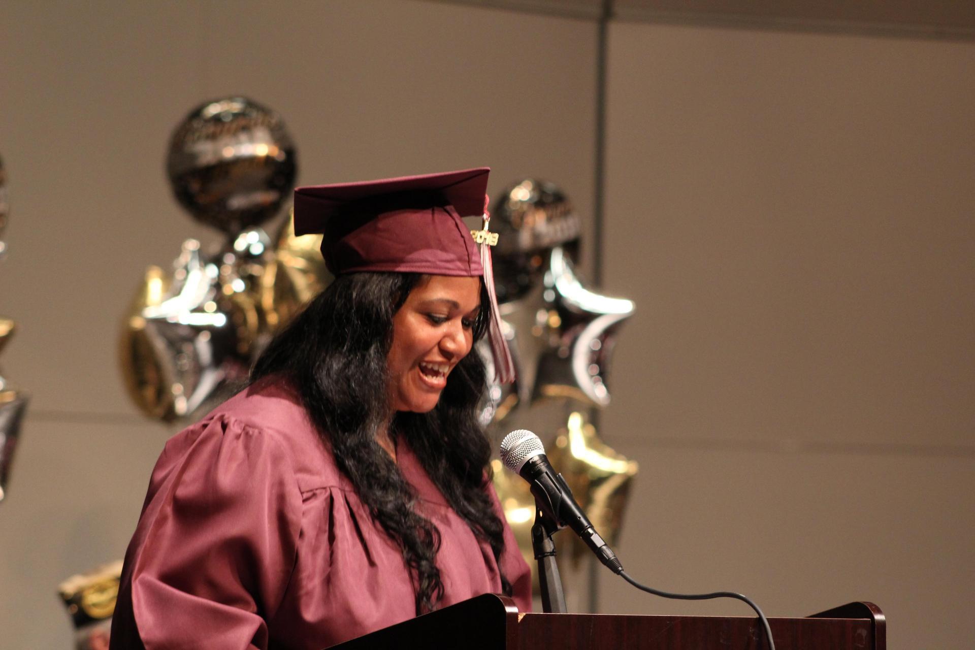 Graduate speaking at podium during graduation ceremony